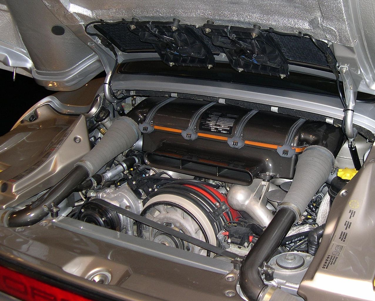 Porsche 959 engine bay revealing the water and air-cooled flat-six engine