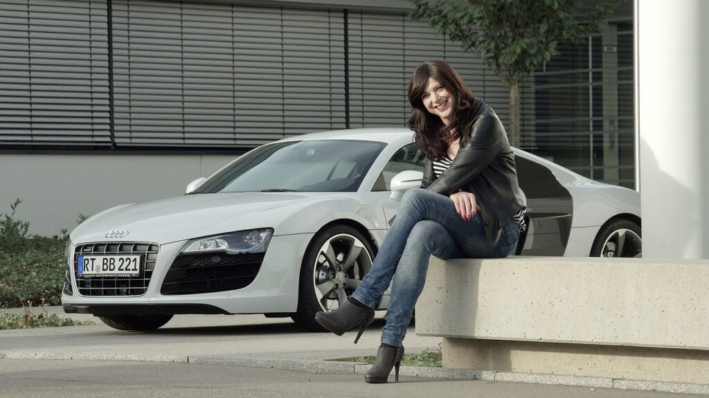 Woman sitting in front of her Audi R8