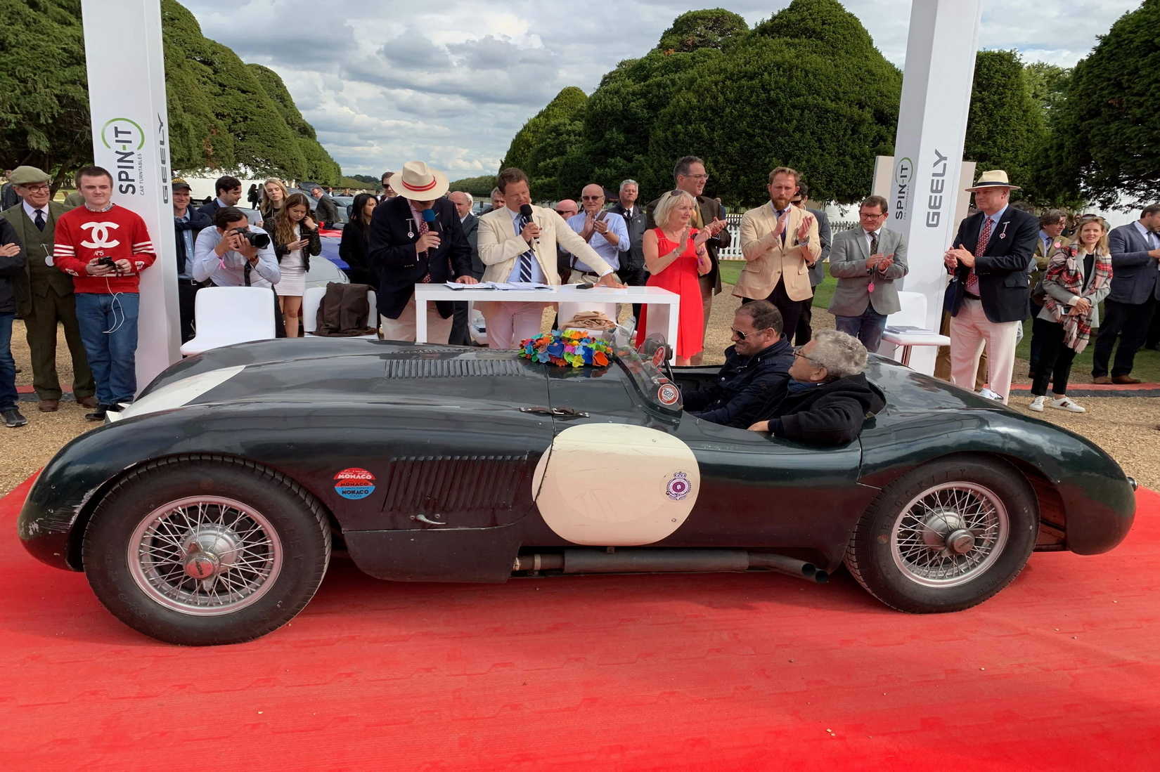 Jaguar C-Type surrounded by a crowd of people at the Concours Stage
