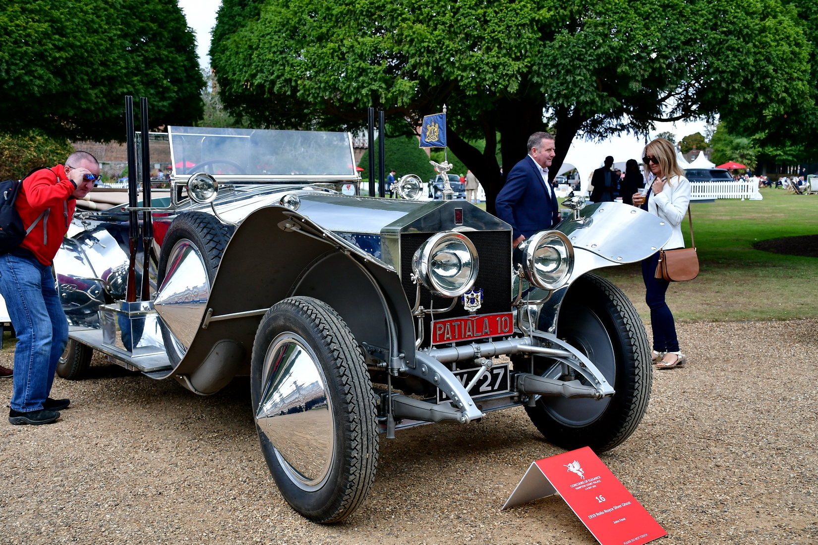 Rolls-Royce Silver Ghost from 1919 with polished aluminium body work adorned with a pair of Partiala 12-bore shotguns outside the driver's door