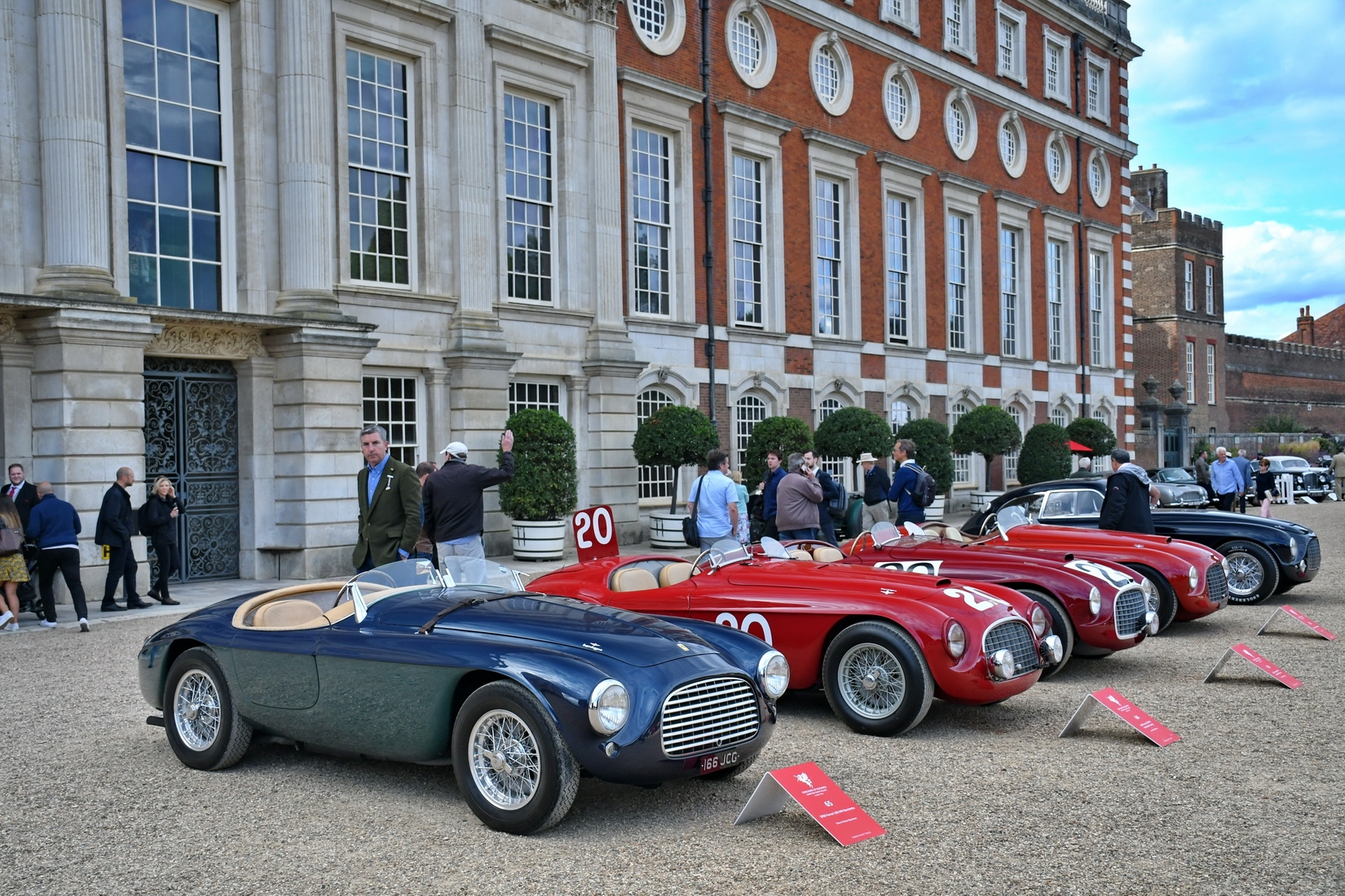 a set of 4 Ferraris 166MM and a 212 Export Berlinetta Touring standing side by side in front of Hampton Court Palace
