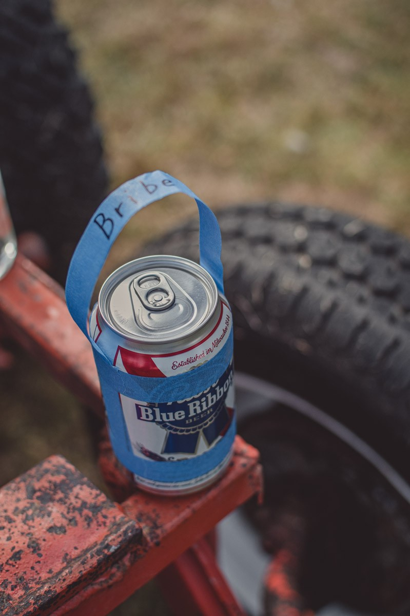 An unopened beer can sitting on a car frame