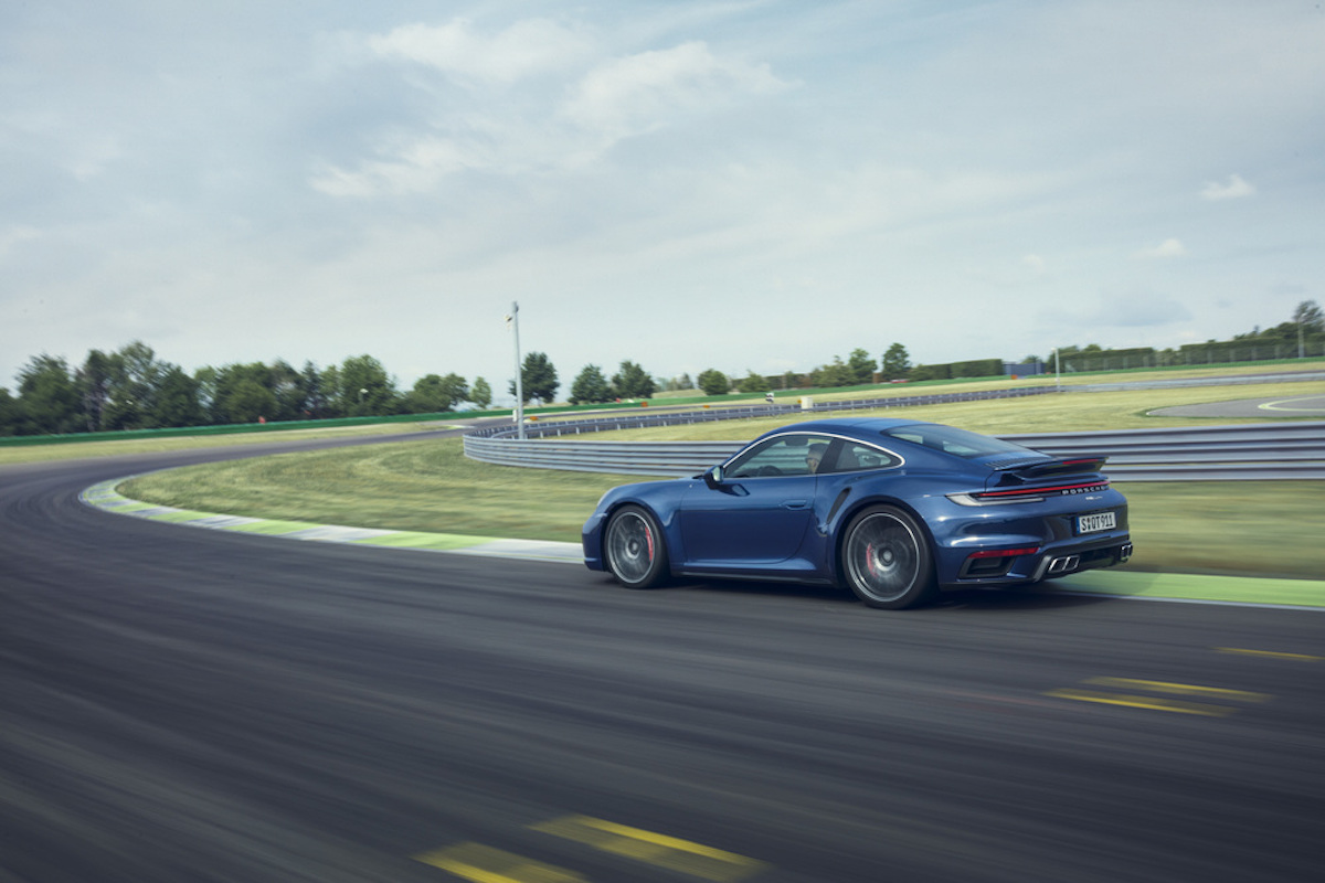 A side/back view of a navy blue Porsche Type 992 911 Turbo S trying out the twisties on a track.