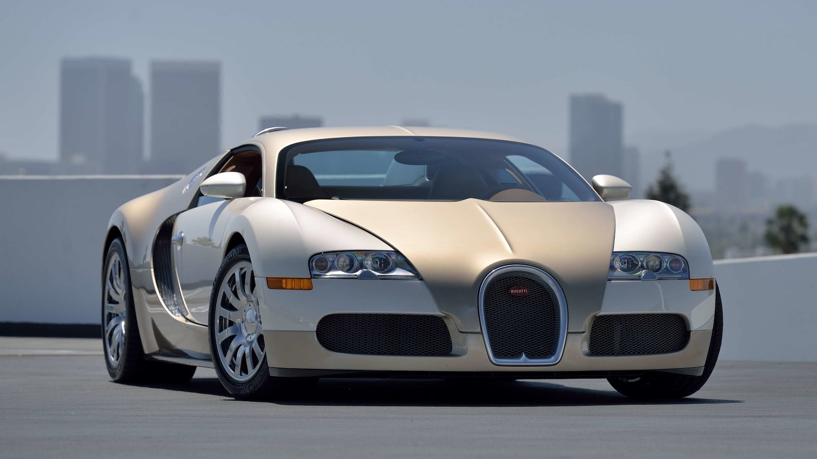 Gold and white Bugatti Veyron on city street with skyscrapers in background