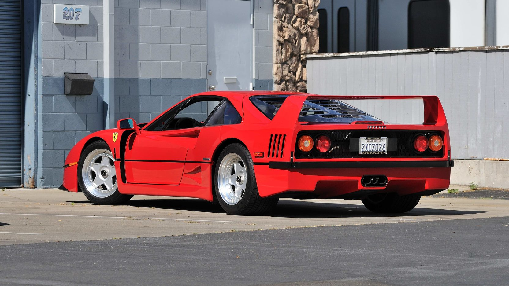 Red Ferrari F40 sitting in parking lot behind building